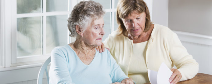 Daughter helping elderly mother with financial information