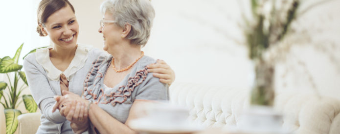 caregiver sitting with senior woman on sofa in woman's home
