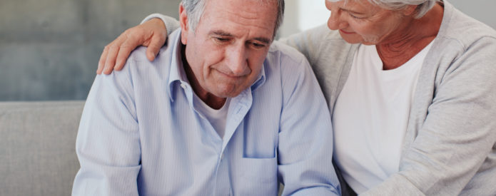 Senior woman comforting her husband