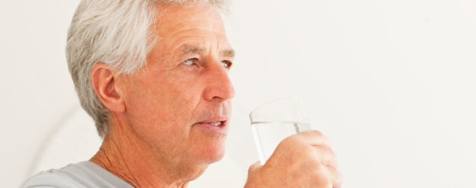 Side view of a retired man holding glass of water