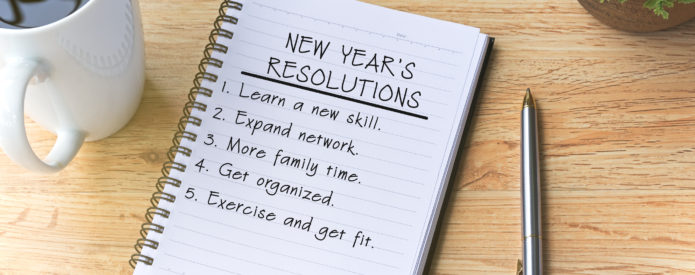 notepad open to page with New Year's Resolutions listed next to cup of coffer and pen