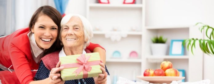 elderly woman receiving a gift from her adult daughter